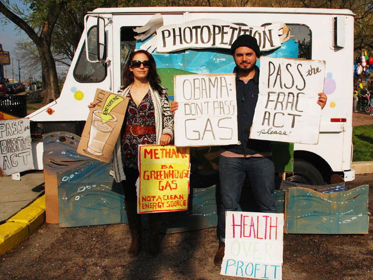 Man and woman stand in front of white milk truck holding protest signs against fracking and urging passage of laws on fracking