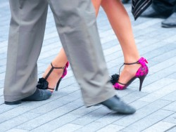 The legs and feet of tango dancers; he wears beige suit, she wears hot-pink and black stiletto heels.