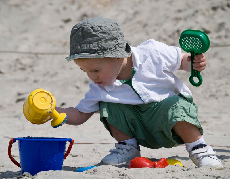 Toddler boy in summer outfit and sun hat squats on sand, holding sand toys and peering into a bucket