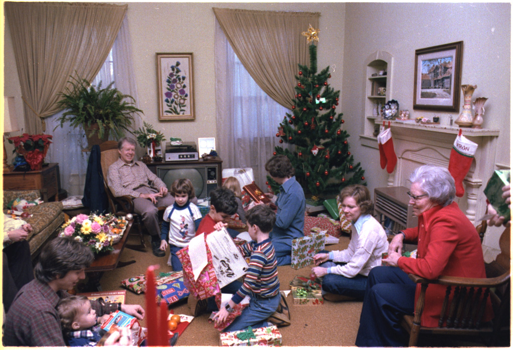 Family in 1970s open presents, 5 kids and 3 adults sit on the floor, 2 older adults sit in chair watching