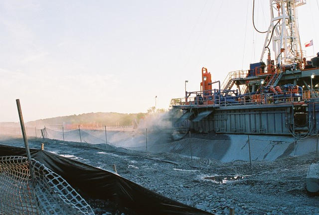 A platform at the base of a drill tower sits at the edge of cement ditch, which is surrounded by mesh fence and gravel