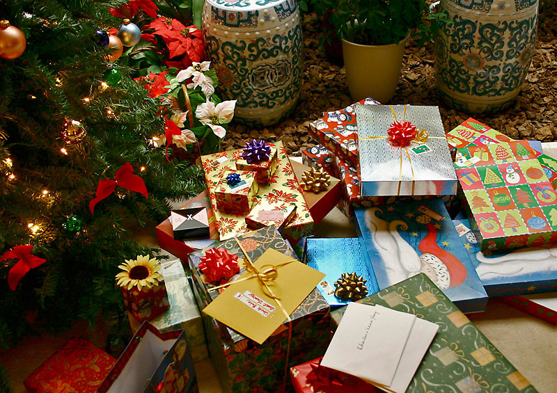 A pile of brightly wrapped gifts lay at the base of a tree decorated with red ribbons and gold ornaments