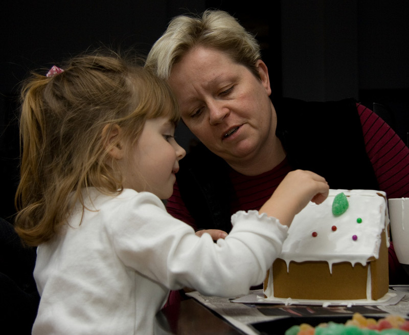 Mother and toddler daughter decorate a gingerbread house