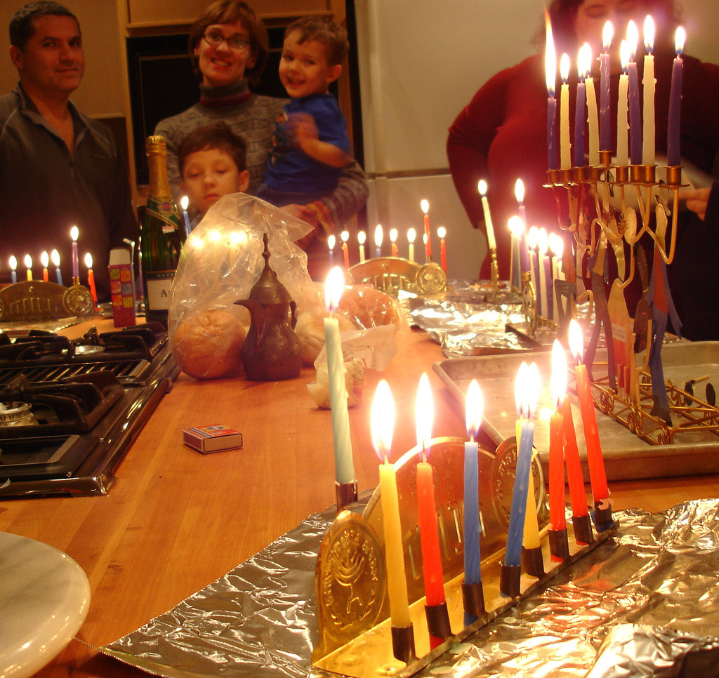 Half dozen menorahs with candles lit sit on kitchen counter, 3 adults and 2 children stand around counter