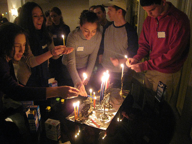 3 women and two men stand at small table and light candles on menorahs, more people stand behind them