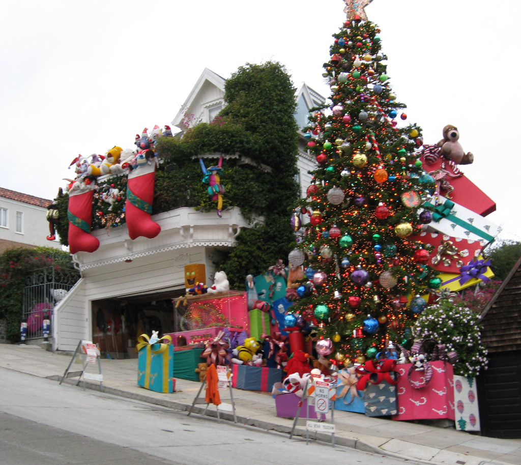 House on steep hill is decked with giant stockings and stuffed animals, huge adjacent tree is laden with decorations and giant gifts