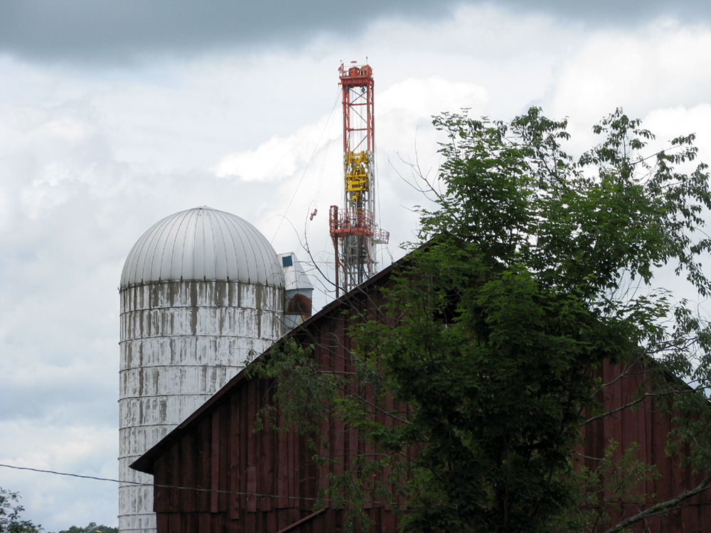A red barn sits in the foreground, a white silo sits behind it, the top of a drilling tower is close behind both.