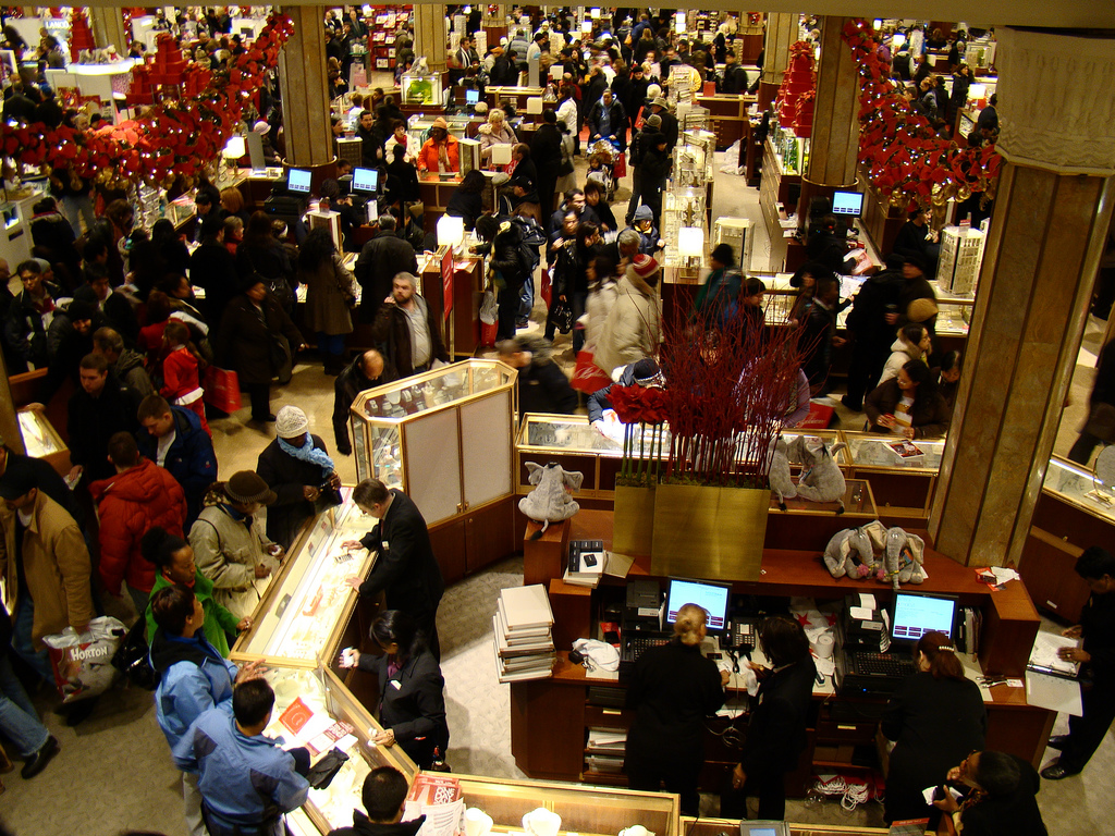 View of busy store floor from above, crowds of people swarm around jewelry displays, red bows hang from pillars