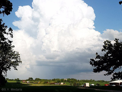 thundercloud hangs low over green fields, blue sky surrounds the storm cell