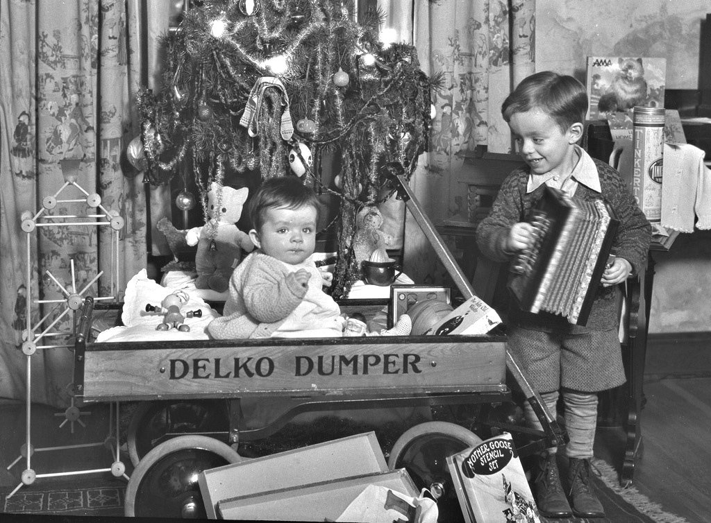 Black and white image of toddler boy playing accordion and baby sitting in wagon in front of Christmas tree