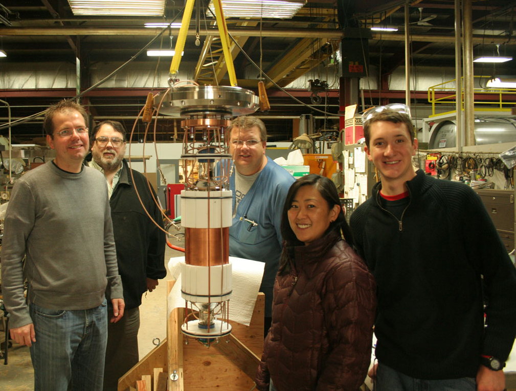 Five smiling people stand around a complex cylindrical device in cluttered industrial lab