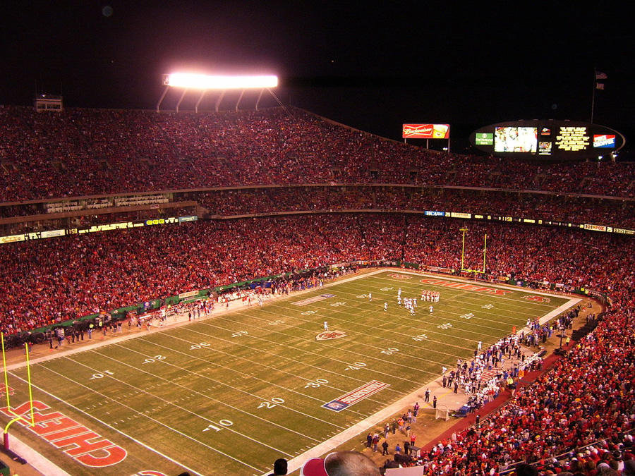 A long view shows the field, with a packed crowd clad in red.