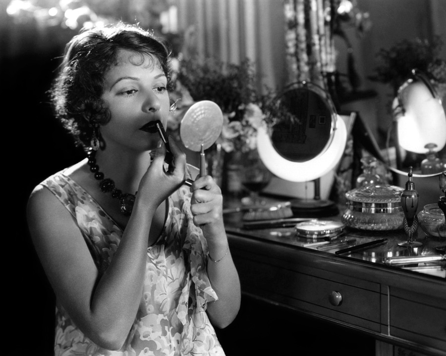 Short-haired woman applies lipstick and looks into hand mirror