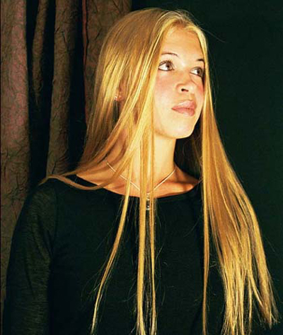 A woman with long blond hair wears a black shirt and stares into the distance with solemn expression.