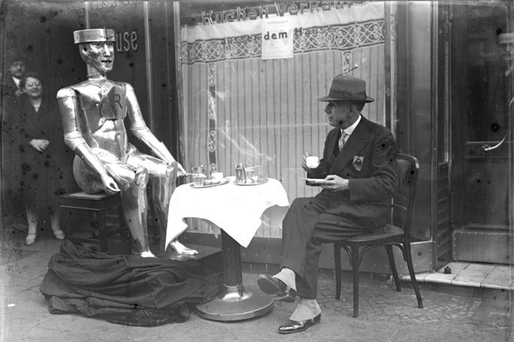 Man in top hat sits drinking tea on a sidewalk with a human-sized robot man, two people look on in background