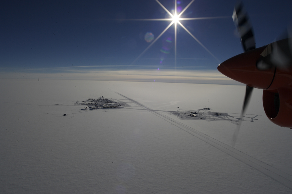 Blue sky with bright sun in upper third; remaining is white land. Propeller entering from right