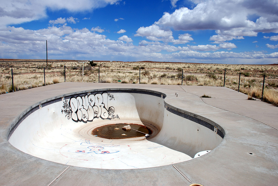 Heart-shaped swimming pool holds a dirty puddle, in a desert landscape. Sky is blue, and partly cloudy