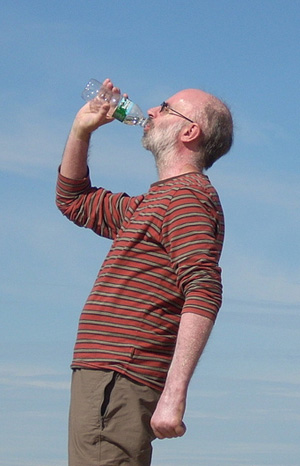 Side view of man drinking from water bottle profiled against blue sky