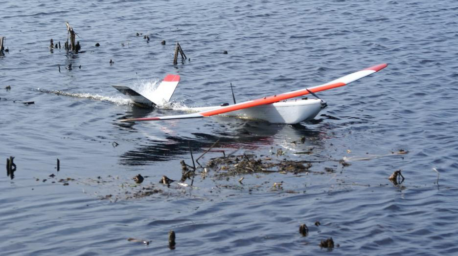 Small white and orange unmanned aerial vehicle landing in water among floating vegetation.