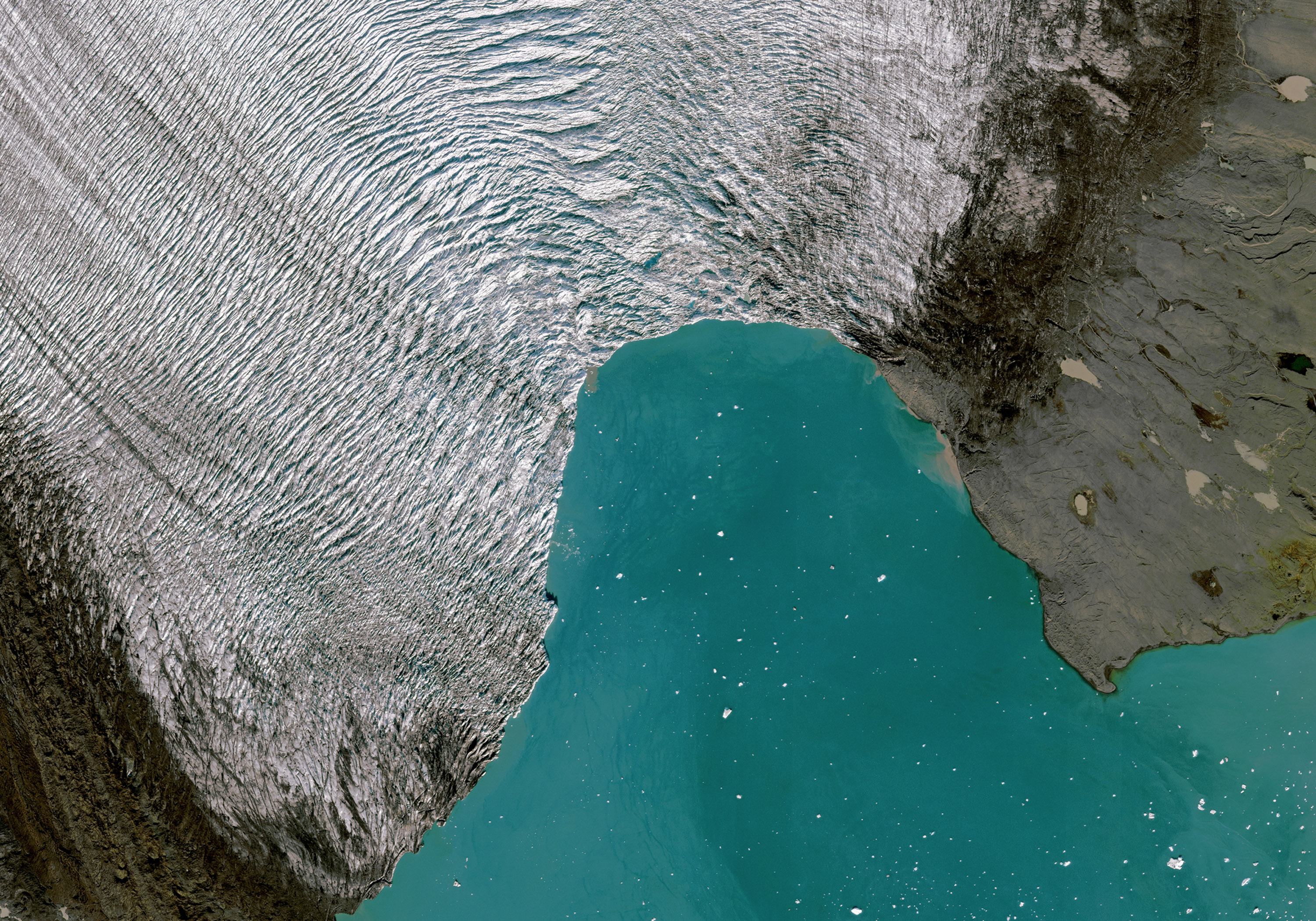 Junction between rough white and gray ice and bright teal water.