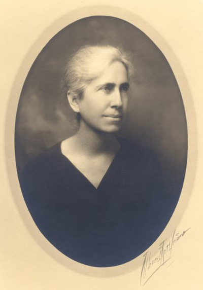 Oval framed portrait of woman in black v-neck with white hair, facing stage left