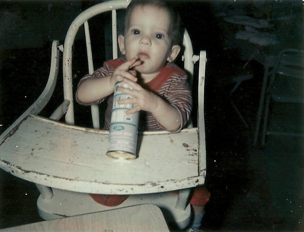 baby playing with aerosol can in high-chair