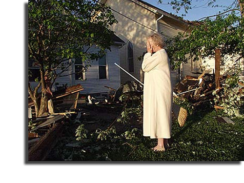 Woman holds her face in her hands amid the devastation