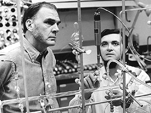 Two men standing, looking at pipes and stands in a chemistry lab.