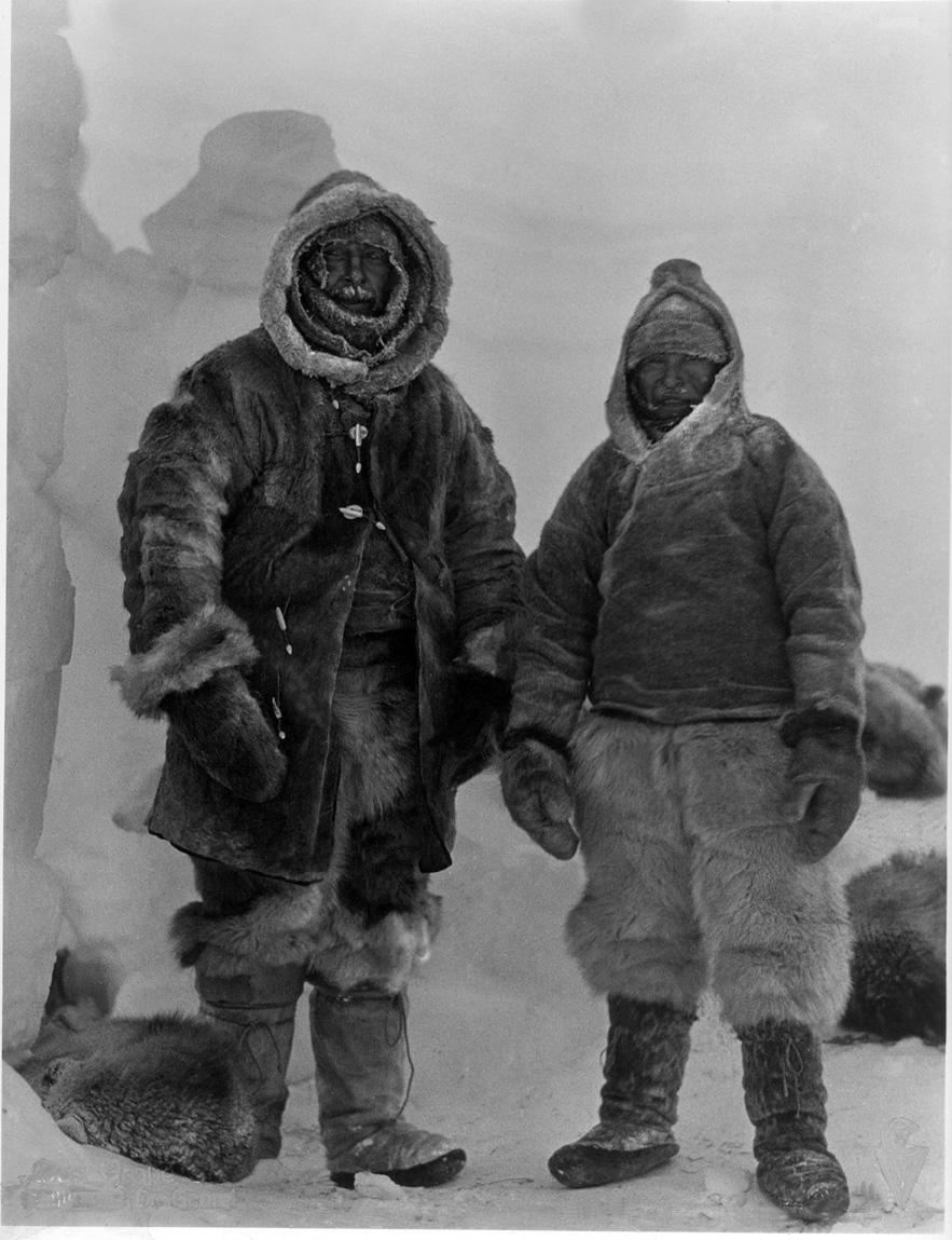 Two men in heavy snow gear standing in front of ice structures posing for picture.