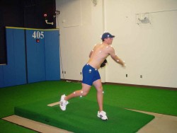 Pitcher, whose joints have white dots on them, on indoor mound just after releasing the ball