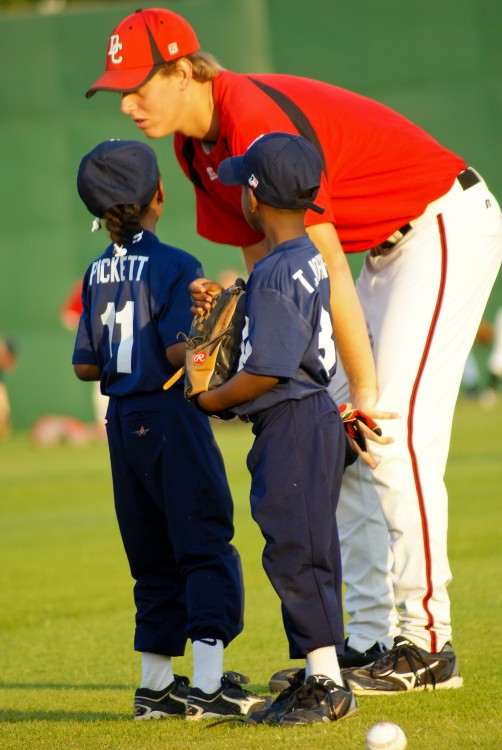 Coach bent over and talking to two young baseball players