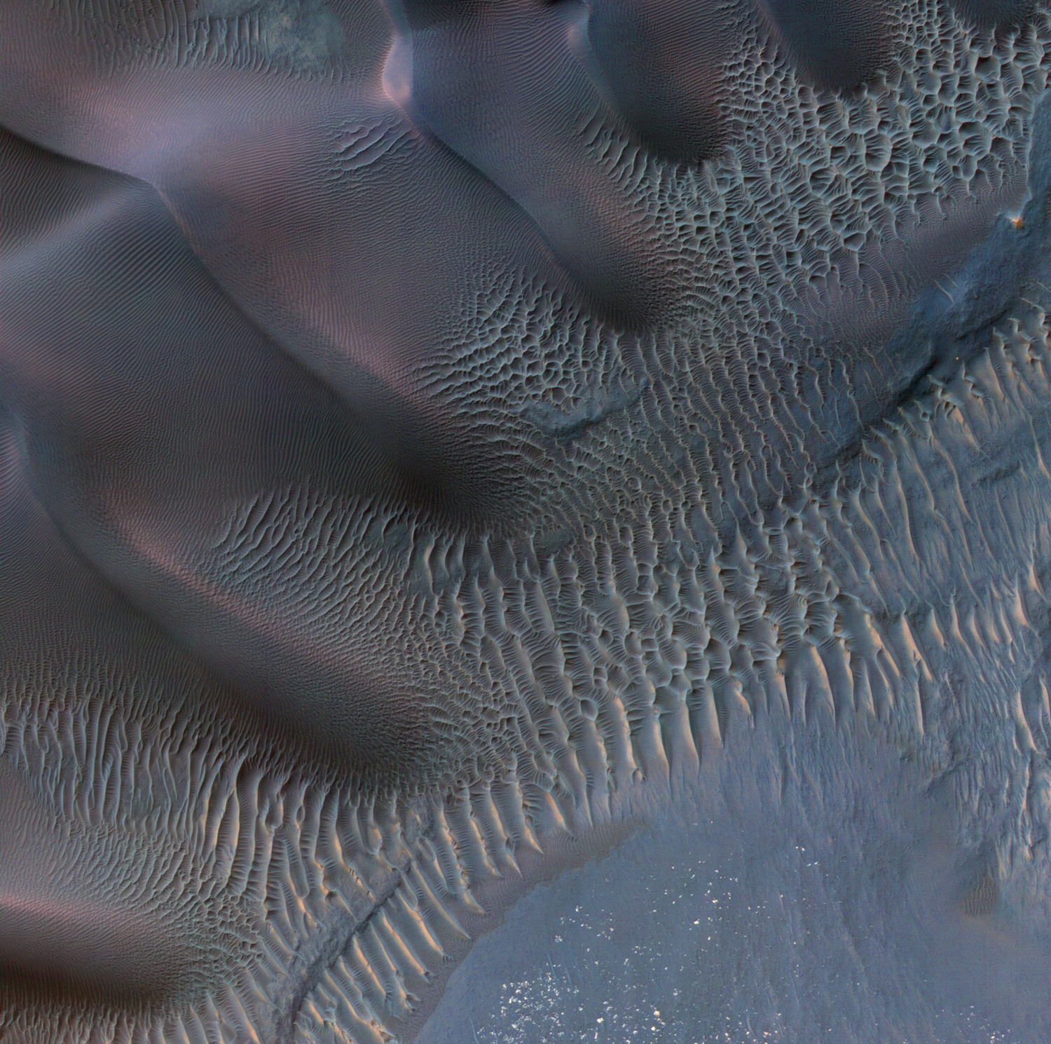 Aerial view of rippled, purple and blue sand dunes