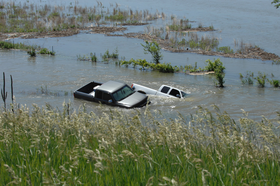 Two trucks sinking in flood waters.