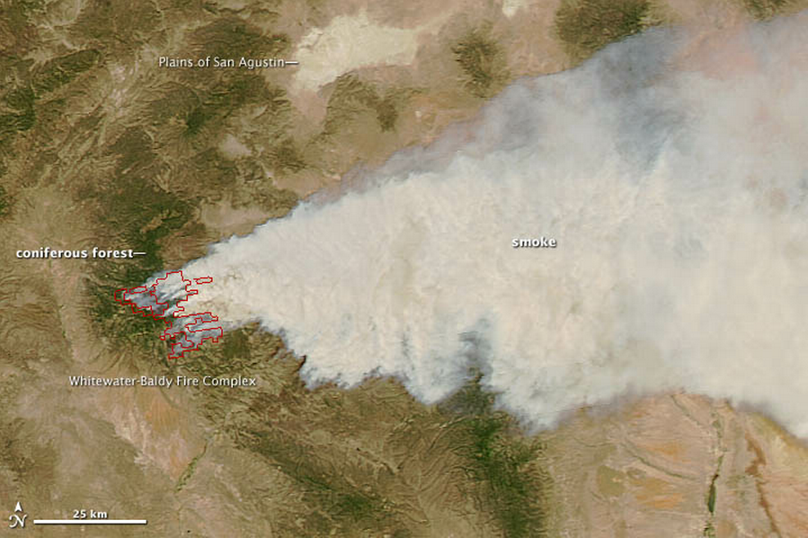 An enormous plume of smoke arises from a brown landscape.