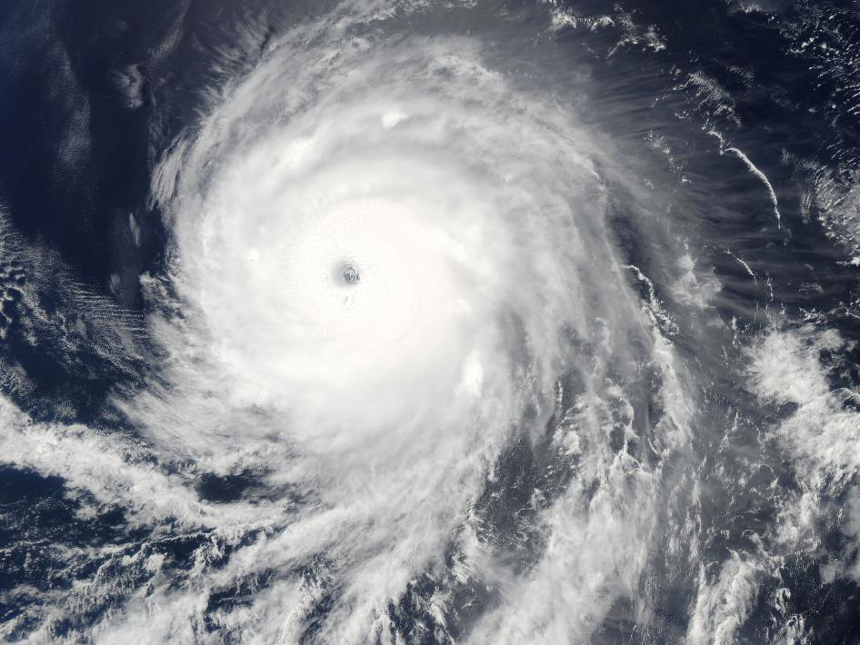 Aerial view of hurricane shows white circle with dark dot (eye) in the center and strings of clouds at the periphery.