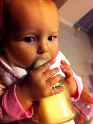 Baby holding and drinking from bottle