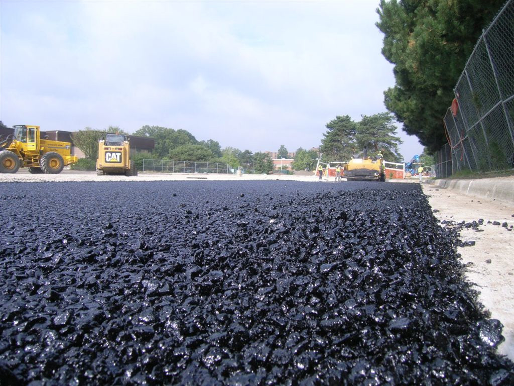 Shiny, knobby black pavement in foreground, construction vehicles in background.