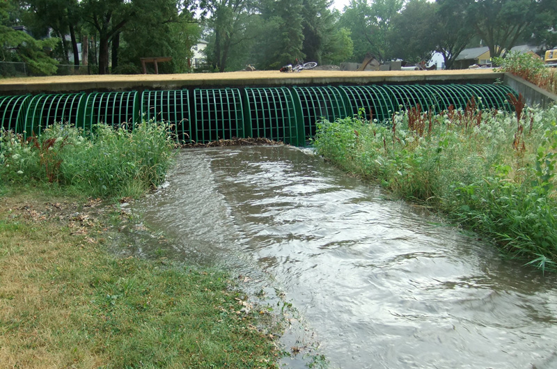 Straight-banked ditch feeds into giant metal grate; water disappears underground.