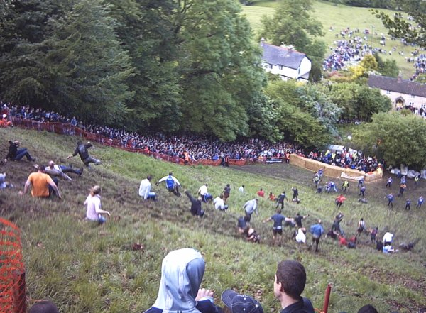 Photo of people stumbling down hill; some upside down. Spectators crowd the sideline.