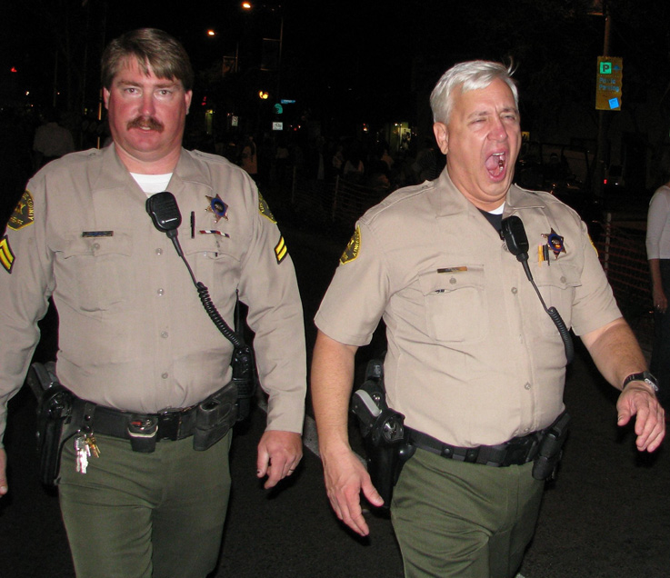 Two cops walk at night; one is yawning
