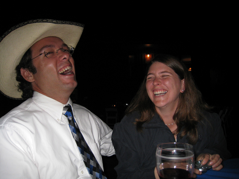 Man in cowboy hat and woman with camera laugh hardily