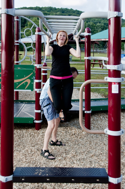 Man holds woman hanging from monkey bars; she smiles uncertainly