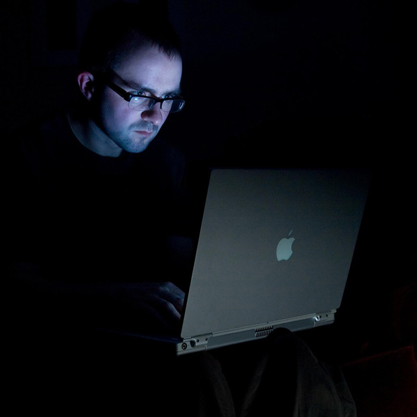Spectacled man sits in dark, stares blankly at computer screen which lights up his face.