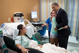 Obama hugs Davies while Young looks on from hospital bed