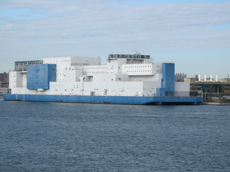 Giant blue and white barge, six stories tall, with small windows
