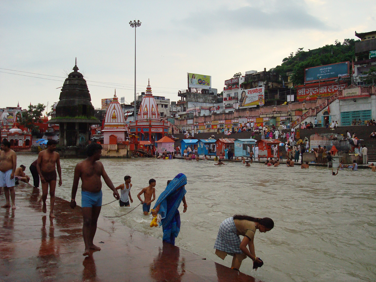 Men and women bathe in river; dome-shaped shrines and colorful huts on other bank.