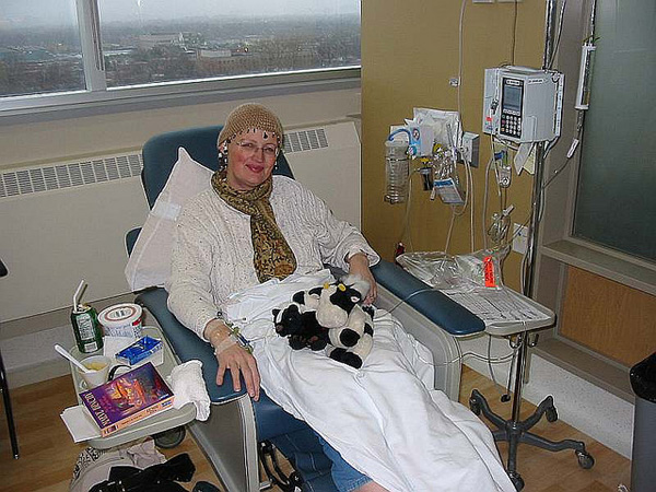 Woman connected to intravenous tubes administering chemotherapy.