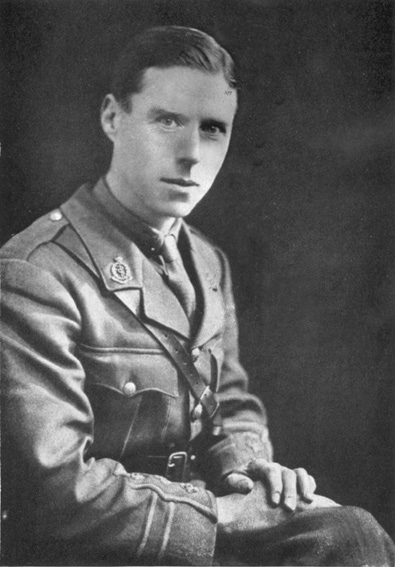 Black and white photo of discoverer of bacteriophage with his hands crossed on his knee, dressed in a British military uniform and looking directly into the camera.