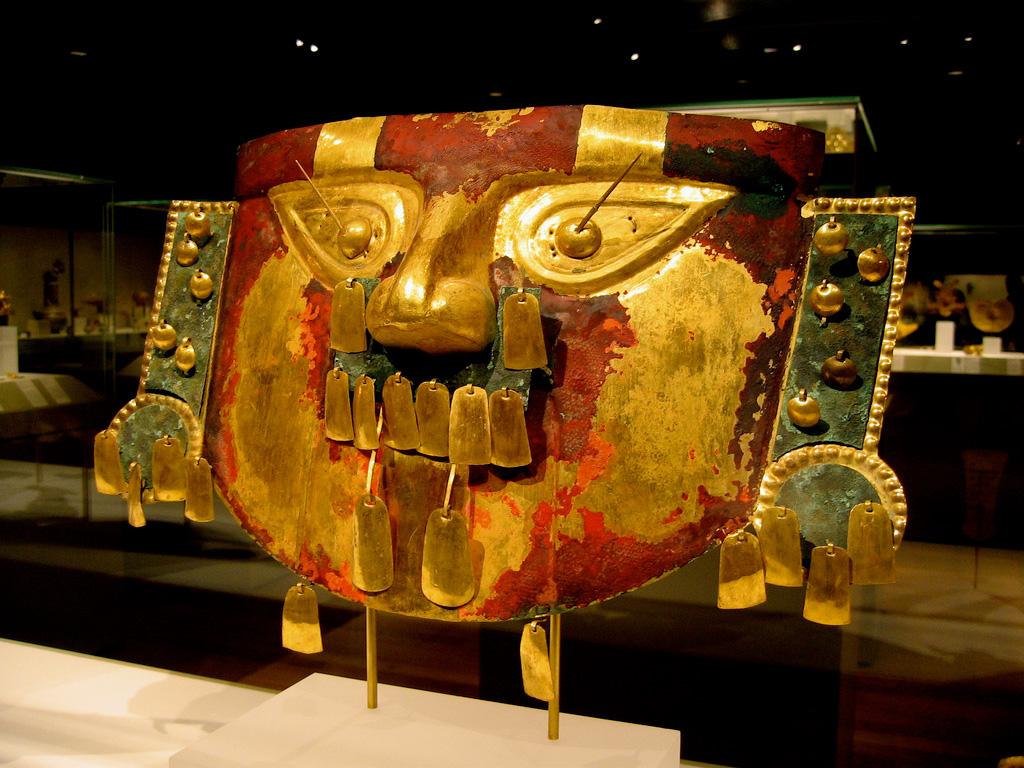 Gold mask decorated with red paint, rectangular gold pendants, and gold disks for eyes.