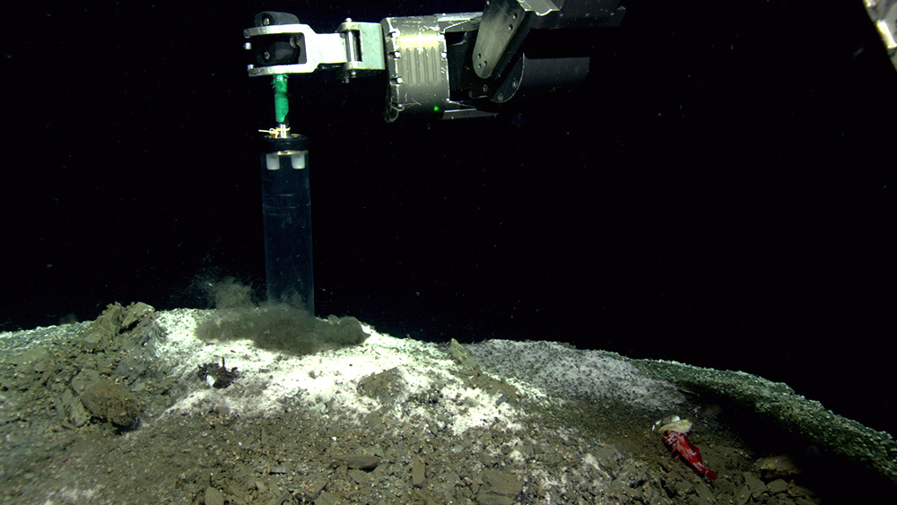 Mechanical arm inserts column into white methane mound on seafloor to take sample